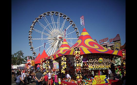 A giant ferris wheel looms over midway prize games