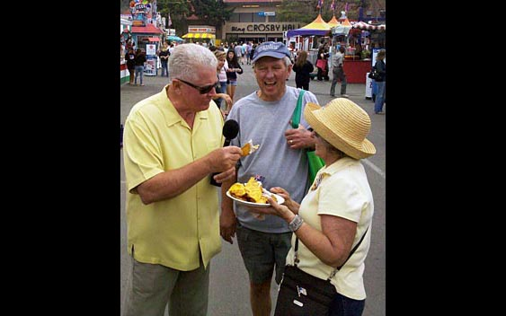 Huell Howser samples a fairgoer's lunch. San Diego County Fair, Del Mar
